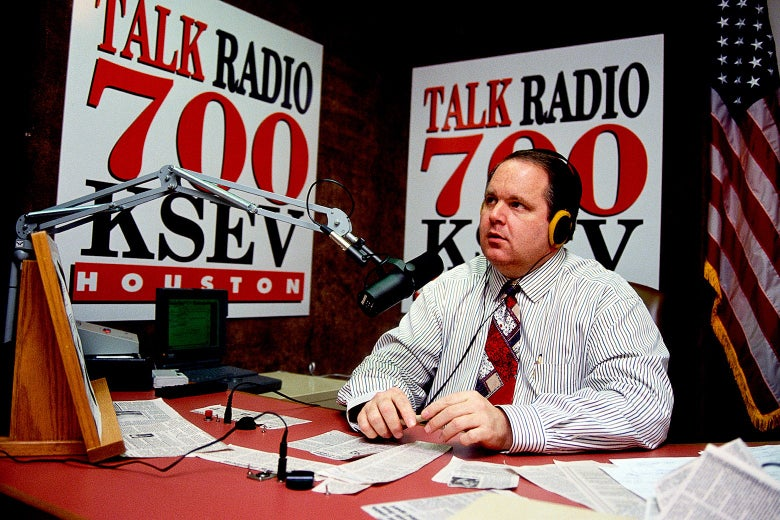 Rush Limbaugh wearing headphones, sitting in front of a mic at a desk covered in newspaper clippings