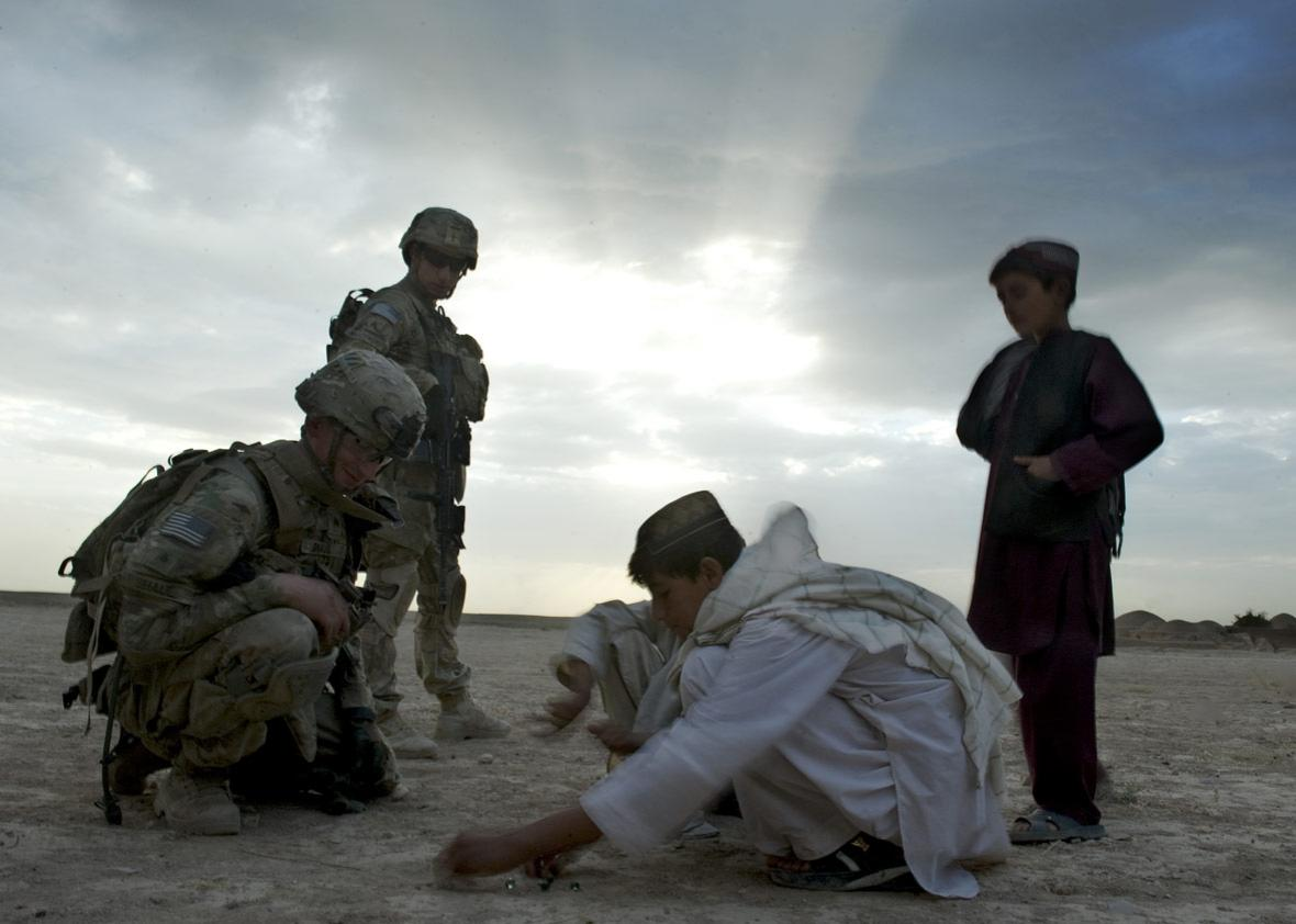 US soldiers from the 1st Platoon, 1-64 Armored Batallion of the US Army, operating under NATO command, interact with Afghan boys
