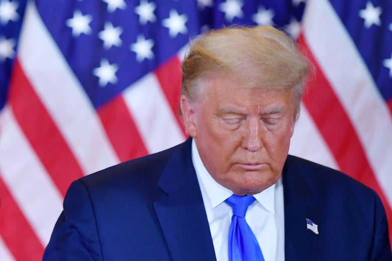 Trump looks down with his eyes closed and an American flag behind him.