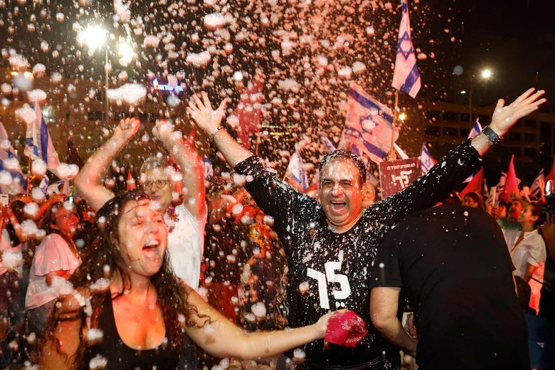 Israeli demonstrators celebrate with foam the passing of a Knesset vote confirming a new coalition government during a rally in the Mediterranean coastal city of Tel Aviv on June 13, 2021.