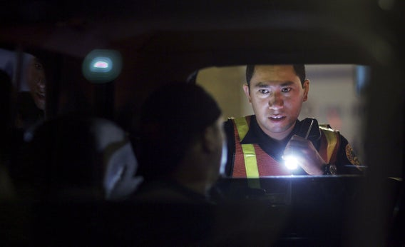 Officer Kevin Millan, from the City of Miami Beach police department, conducts a field sobriety test at a DUI traffic checkpoint.