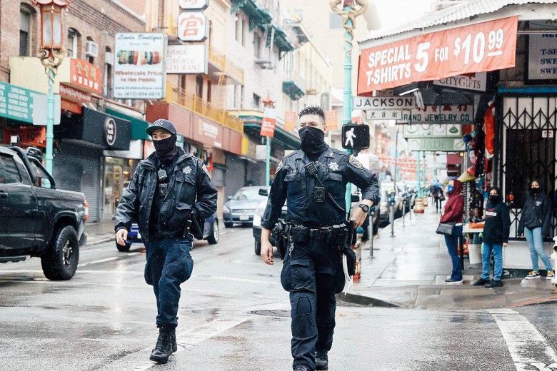 Two police officers wearing black gaiters walk through Chinatown