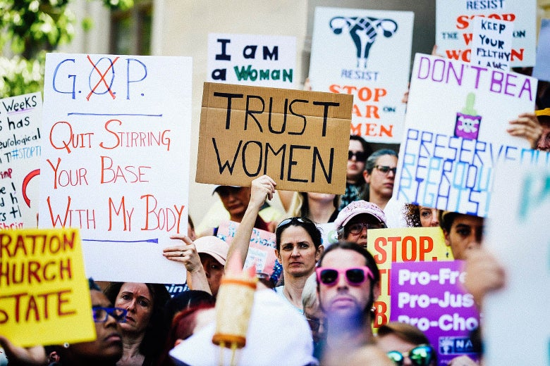 "Protesters hold signs opposing the abortion ban: ""TRUST WOMEN,"" ""GOP QUIT STIRRING YOUR BASE WITH MY BODY,"" and more."