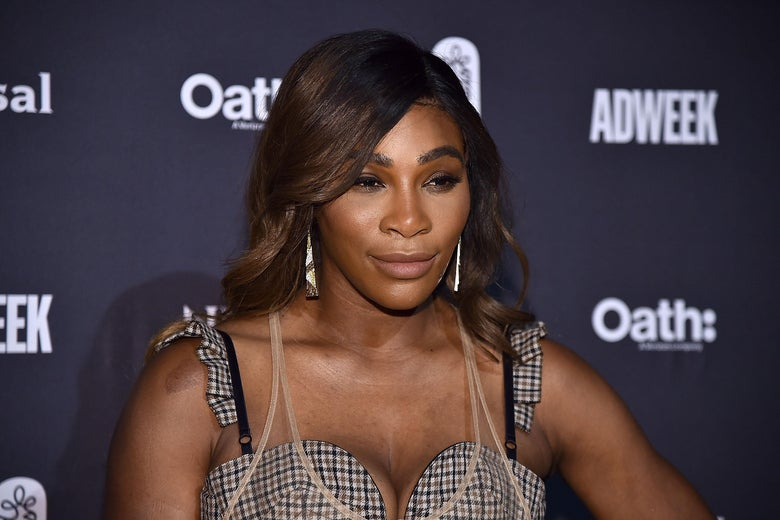 Serena Williams stands against a black backdrop, wearing a plaid sleeveless dress.