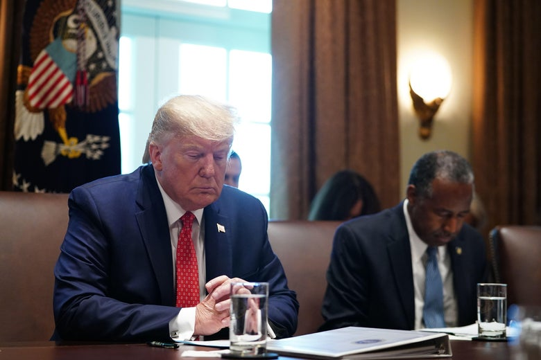 Trump nods his head and closes his eyes in apparent prayer next to HUD Secretary Ben Carson who is doing the same thing.