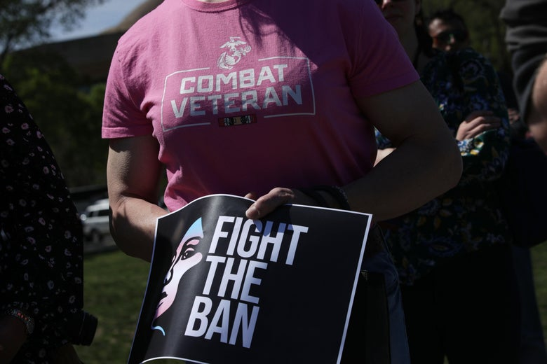 "A person wearing a ""Combat Veteran"" T-shirt holds a sign that says ""Fight the Ban."""