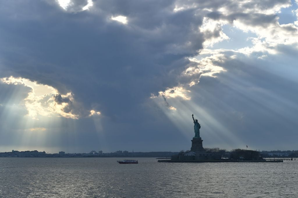 Rays of sunshine shine on the Statue of Liberty and New York Harbor from behind a cloud in the late afternoon.