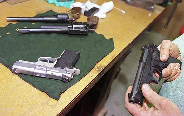 Man examining handgun at his home, Westminster, Colorado.