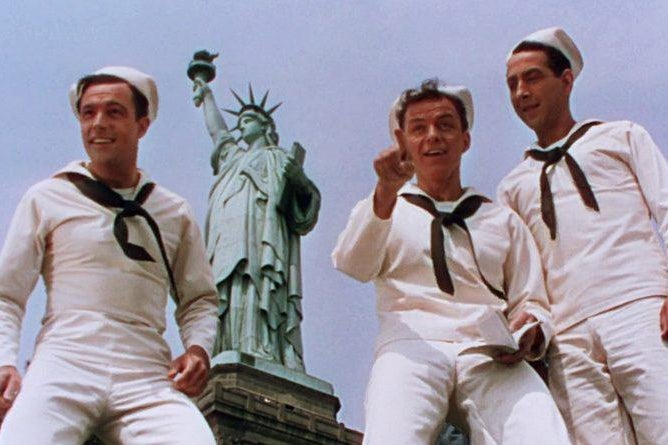 A still of Gene Kelly, Frank Sinatra, and Jules Munshin by the Statue of Liberty in On the Town.