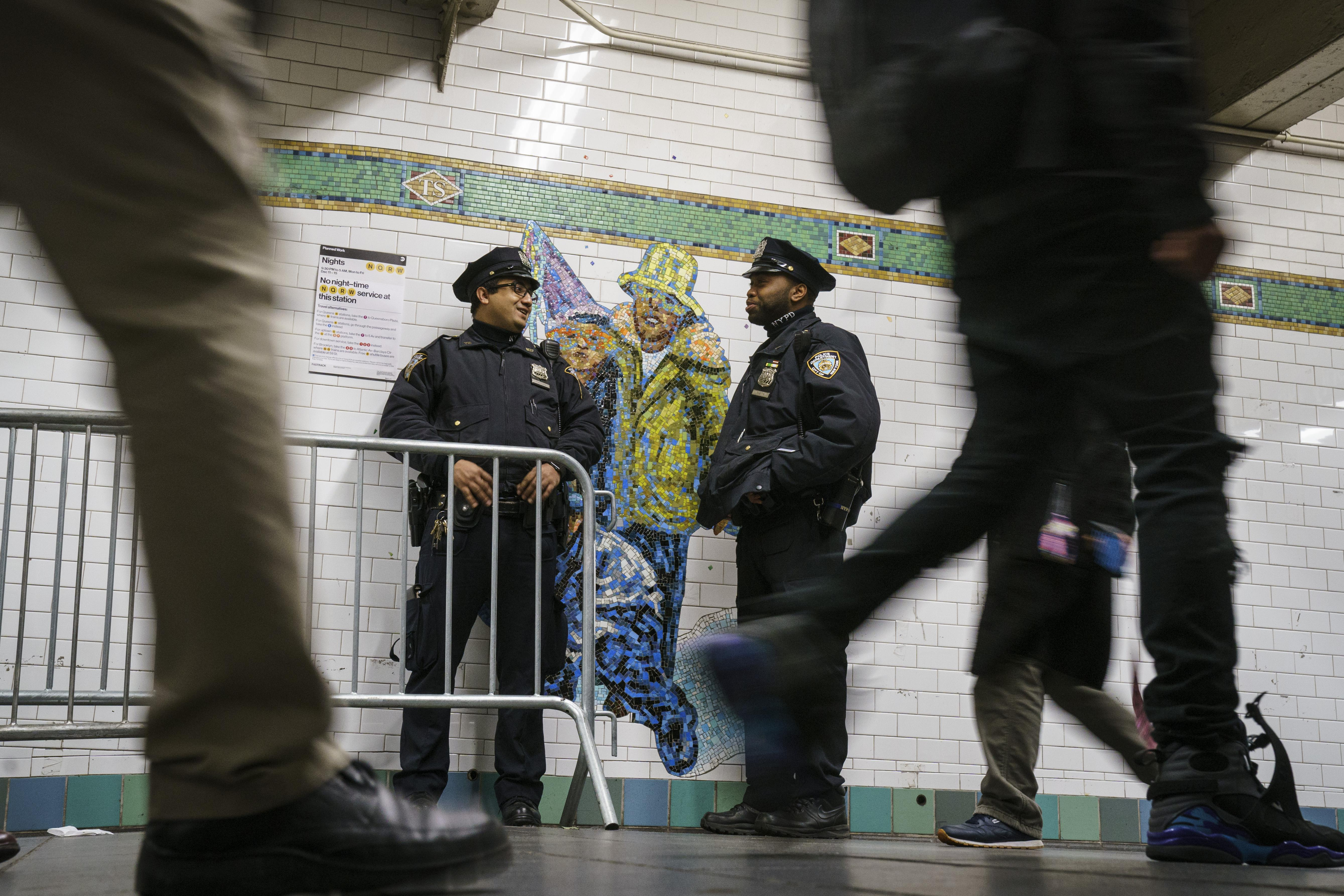 NEW YORK, NY - DECEMBER 12: Police officers stand guard as commuters make their way through the passageway connecting the Times Square subway station to the Port Authority subway station and bus terminal, near the site of Monday morning's attempted terror attack, December 12, 2017 in New York City.  Akayed Ullah is in custody for an attempted terror attack after an explosion in a passageway linking the Port Authority Bus Terminal with the subway during rush hour. (Photo by Drew Angerer/Getty Images)