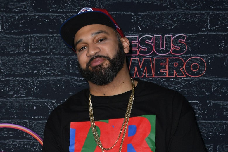 He wears gold chains, a black T-shirt, a beard, and a cap with a flat brim.