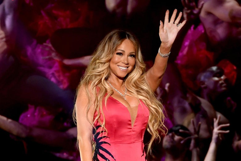 Mariah Carey stands on stage in a pink dress and gives the crowd a joyous wave and smile.