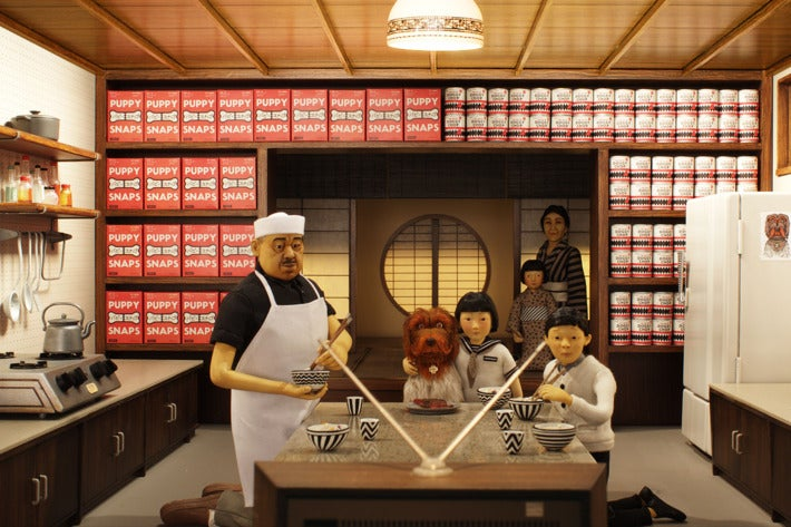 A Japanese family (complete with dog) sits at a dining room table and watches TV in Wes Anderson's Isle of Dogs.