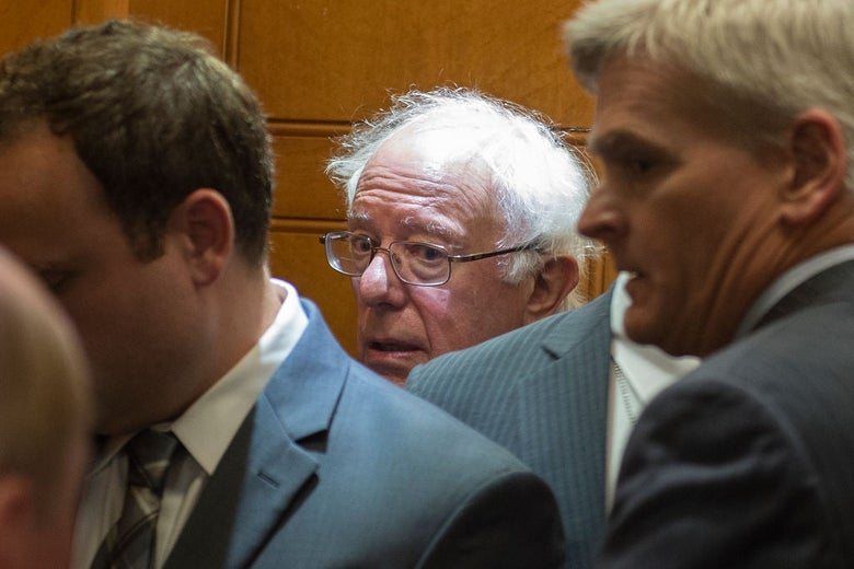 Sanders looks toward the camera with a beleaguered expression on his face in a crowded elevator.
