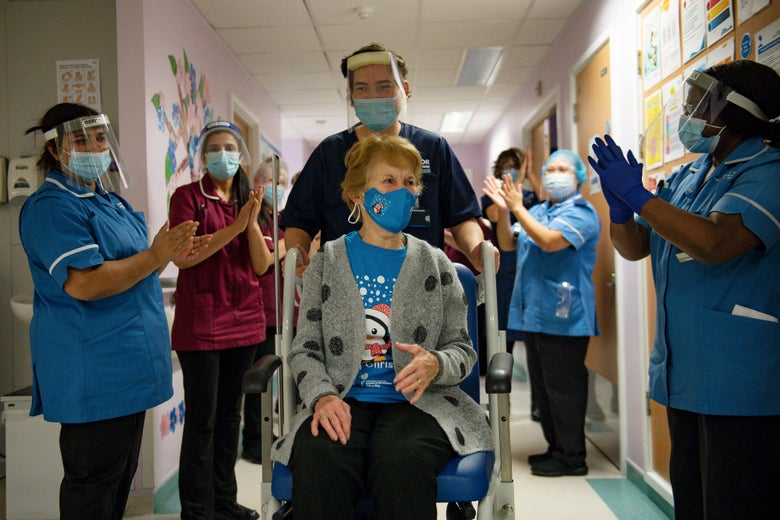 A woman in a wheelchair surrounded by medical professionals clapping