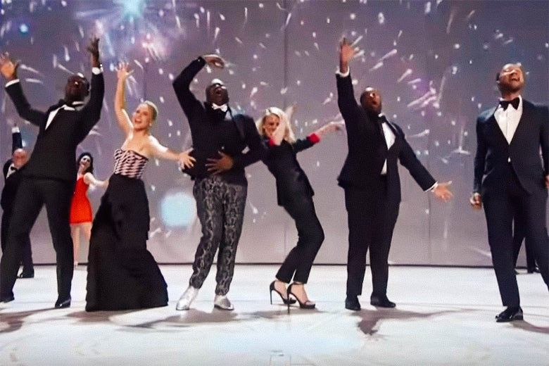Fireworks go off on a projection screen behind a bunch of dancing TV stars.