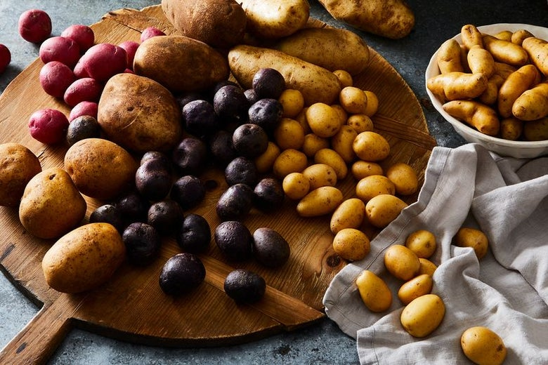 A variety of potatoes, small, large, red, brown, round, and tuberous, on a wooden platter.