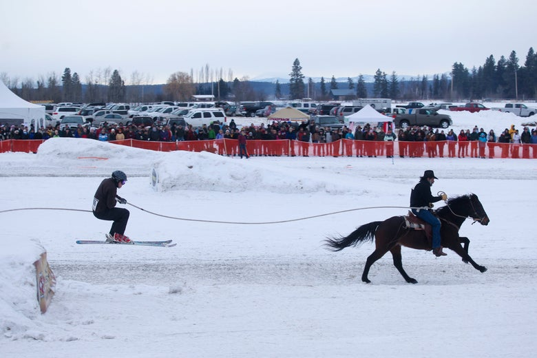A man on skis is tethered to a horseback rider, who is pulling him off an elevated jump on a snow-covered hill.