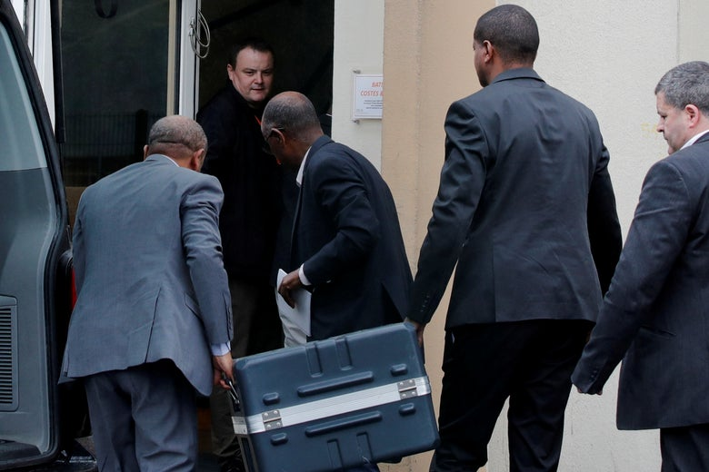 Men unload a case containing the black boxes from an SUV
