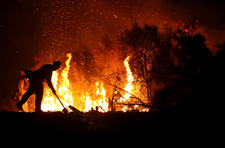 A firefighter battles a wildfire.