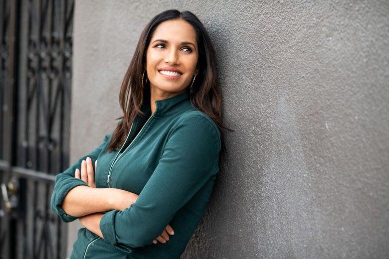 Padma Lakshmi leaning against the wall smiling