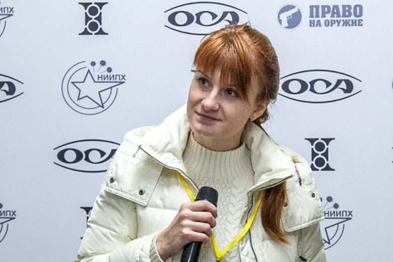 Butina, seated, holds a microphone at a press conference.