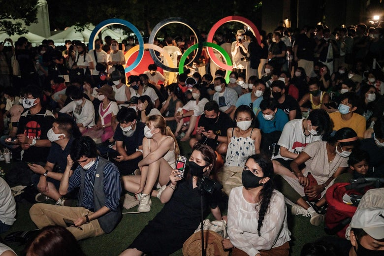 A crowd of people wearing masks watch the live stream of the opening ceremony of the Tokyo 2020 Olympic Games on smart phones next to the Olympic Stadium in Tokyo on July 23, 2021.