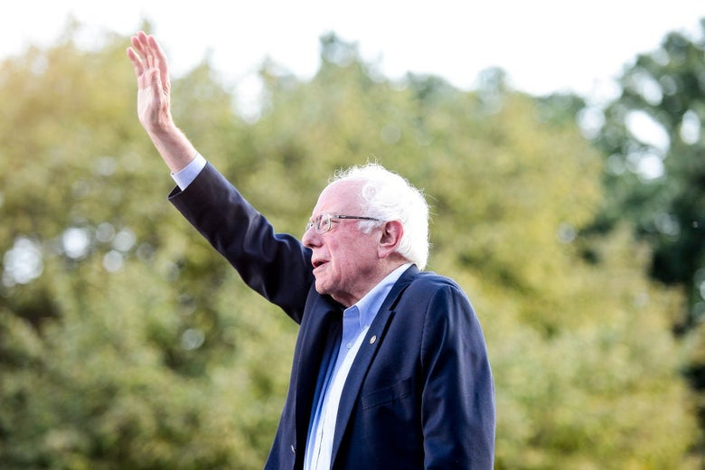 Sanders, wearing a blue suit without a tie, waves to a crowd against a backdrop of trees.