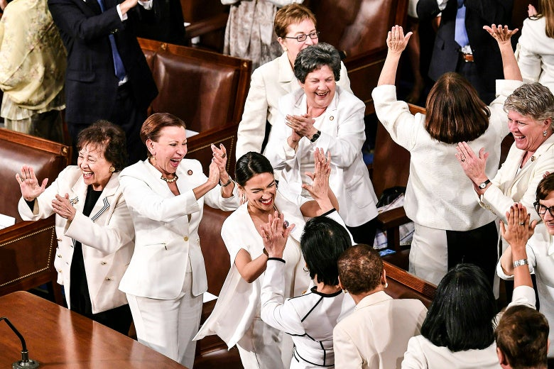 The congresswomen, all dressed in white, cheer and clap.