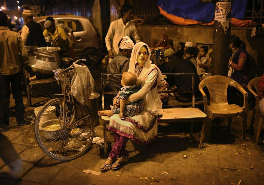 An Indian Muslim woman holds her child as she waits on a bench at a food stall in New Delhi, India, on March 14, 2013.