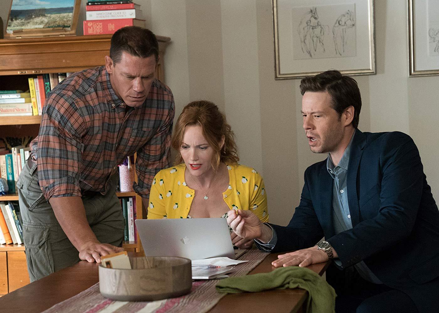 Leslie Mann, Ike Barinholtz, and John Cena huddle around a laptop.