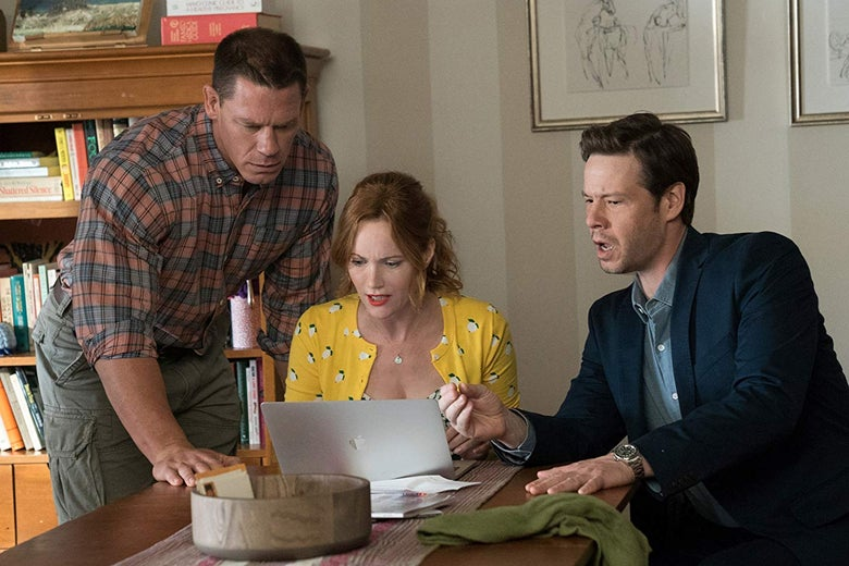 Leslie Mann, Ike Barinholtz, and John Cena huddle around a laptop.