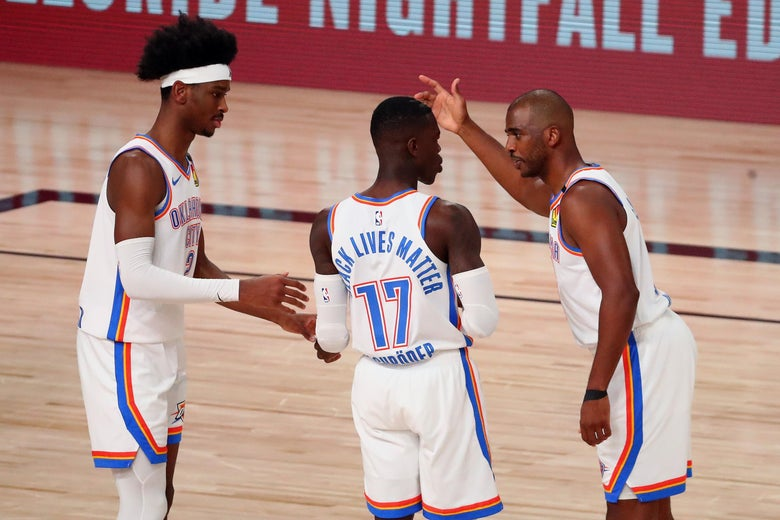 Three Oklahoma City players stand together conversing on the basketball court.