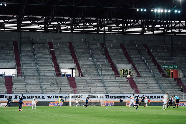 People play in a soccer field with empty bleachers.