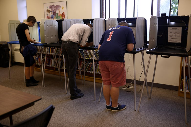 People stand at voting booths in a library.