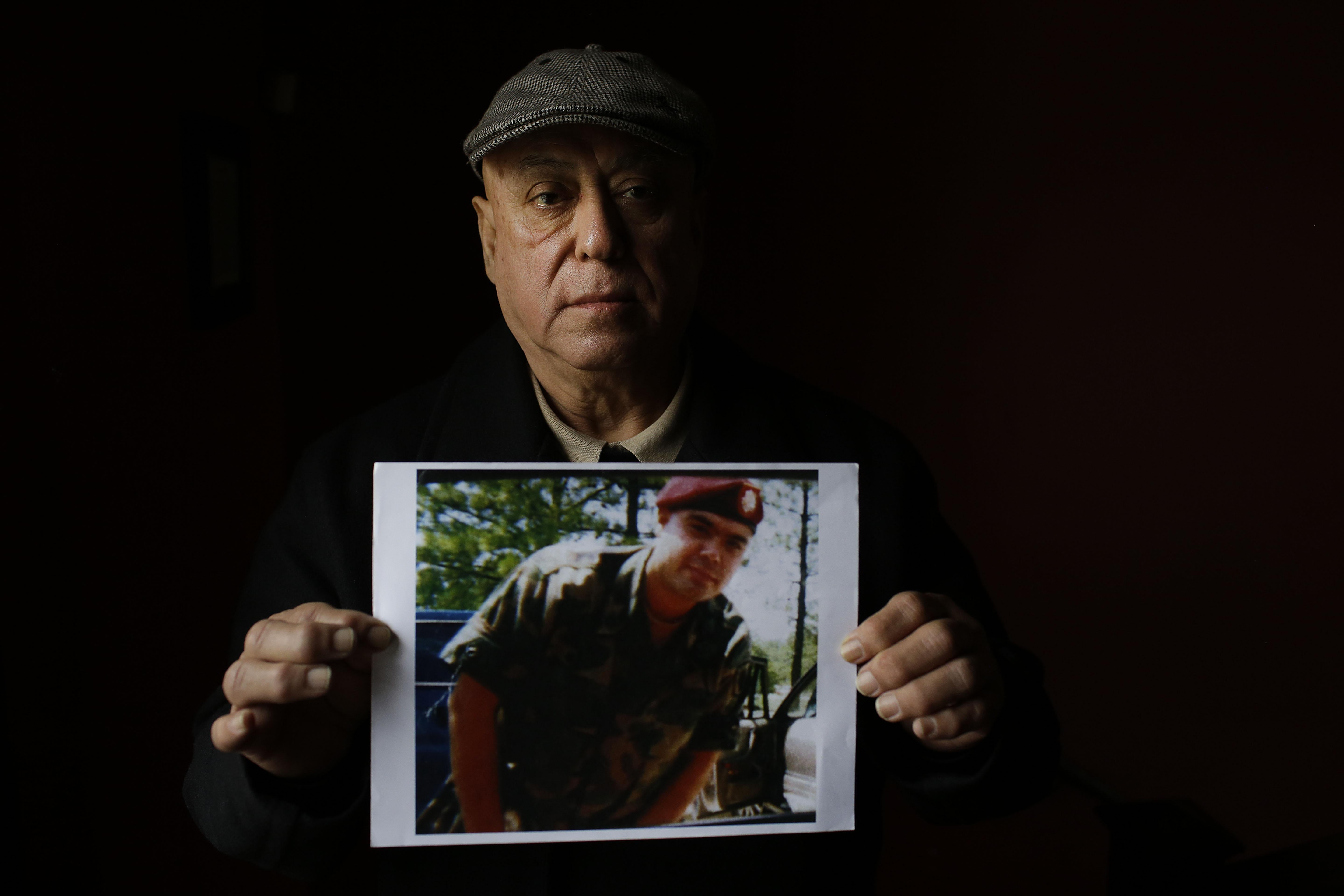 Miguel Perez poses as he holds a photo of his son Miguel Perez Jr., on April 4, 2017 in Chicago, Illinois.