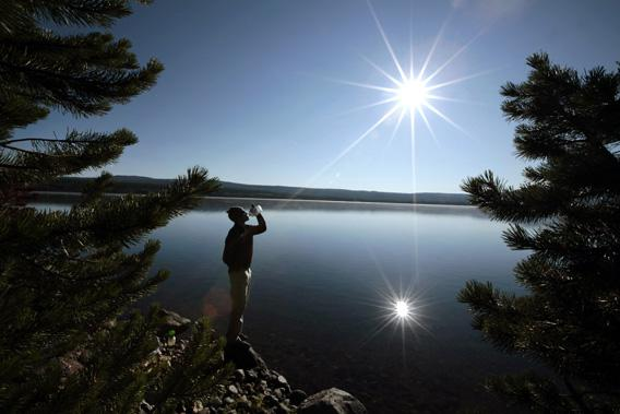 A hiker drinks from a water bottle in front of Heart Lake in the Red Mountains of Yellowstone National Park, Wyoming.