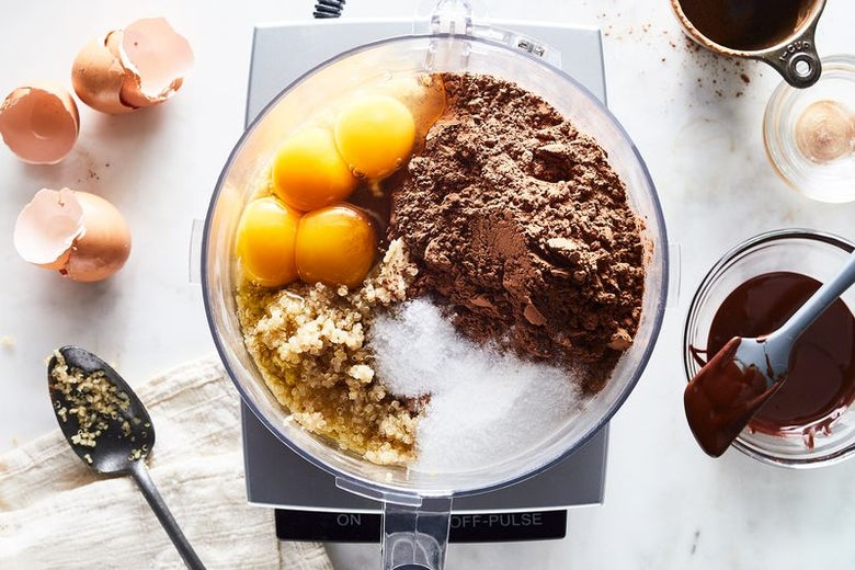 Ingredients for the cake (eggs, cocoa, quinoa, sugar) sit in a food processor next to a bowl of ganache.
