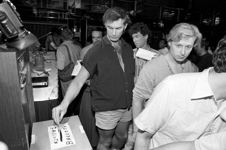 A black-and-white photo of John Sayles putting a ballot in a box.