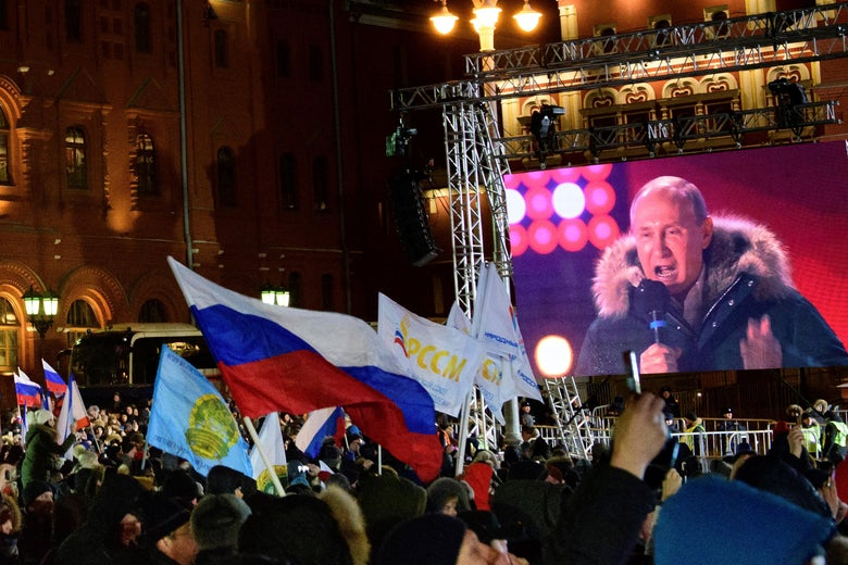 People listen to President Vladimir Putin during a rally and a concert celebrating the fourth anniversary of Russia's annexation of Crimea at Manezhnaya Square in Moscow on March 18, 2018.
