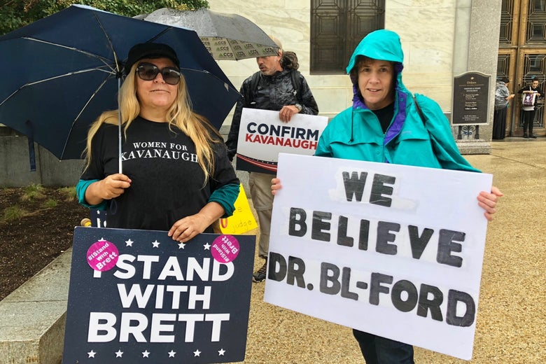 Lourdes Washington (left) and Abby Bolt (right) holding up signs with opposing views in front of the Dirksen Senate Office Building, where the hearing was held. Washington supported Kavanaugh and Bolt supported Ford.
