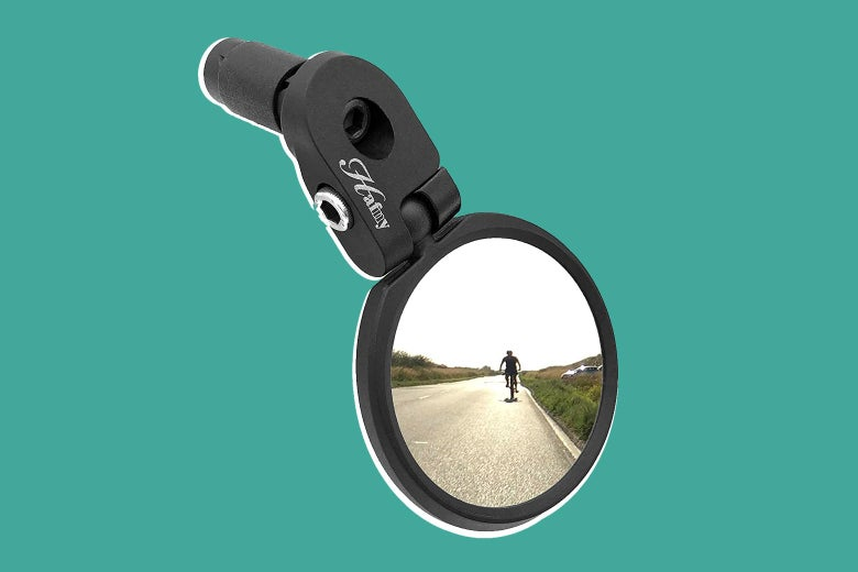 A bike mirror with a biker's reflection in it on a teal background.