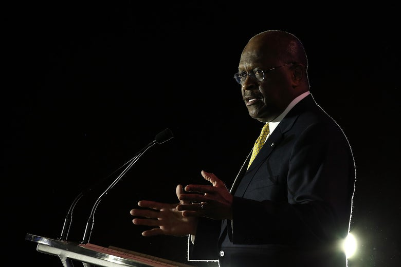 Cain speaks at a podium on a dark stage