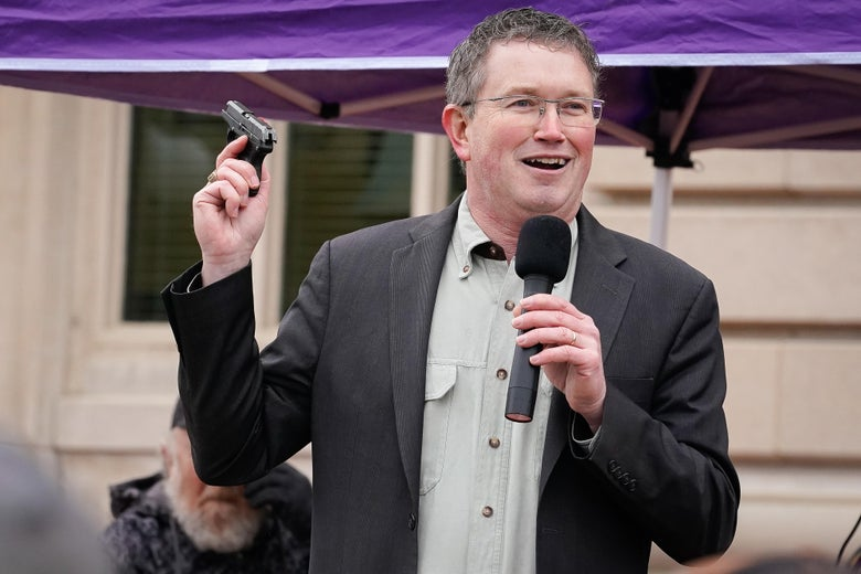 Thomas Massie holds a microphone and a gun.