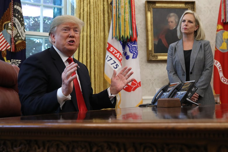 Trump, seated at a desk, gestures while speaking. Nielsen stands in the background.