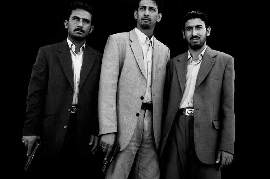Ali Abdul Hussein, left, Mohammed Abdul Redha, center, and Ahmed Khalaf, right, Shiites loyal to Muqtada al Sadr, stand for a portrait in Baghdad, Iraq on March 2, 2006.  They work in the local office of Muqtada Al Sadr who, after a Sunni mosque was attacked, helped to secure it. The invasion of Iraq broke a community into sectarian halves, at each other?s throats: Sunni and Shiite, who have lived together -- albeit not in perfect harmony -- for 1400 years became mortal enemies, killing each other?s women and children.