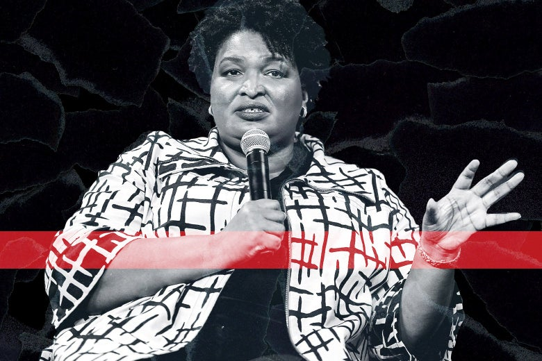Stacey Abrams holds a microphone.