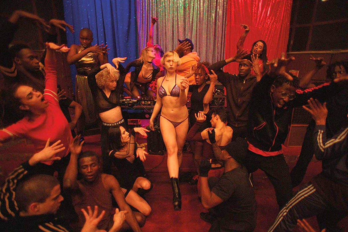 A still from Climax: a dance scene featuring people in various stages of enjoyment while the central blond figure struts forward in black boots, a purple bikini.
