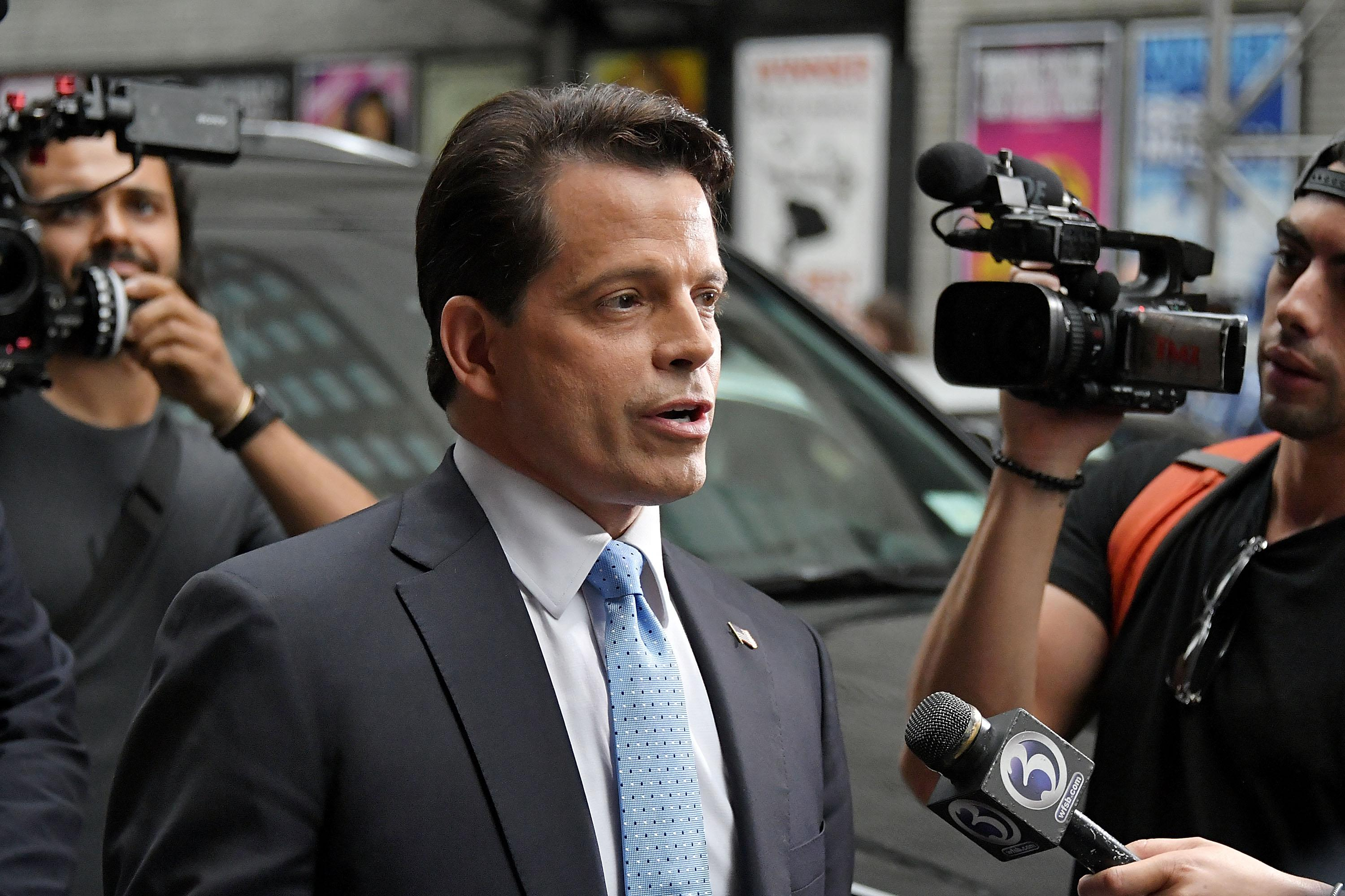 Anthony Scaramucci surrounded by cameras on a New York City street.