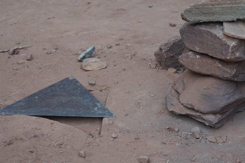 A triangular piece of metal next to a cairn